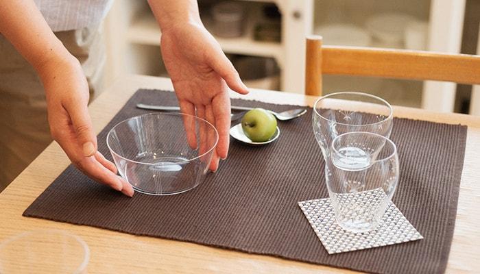 食卓にセットされた木村硝子店のうすはりガラスのボウルに女性が手を添えている