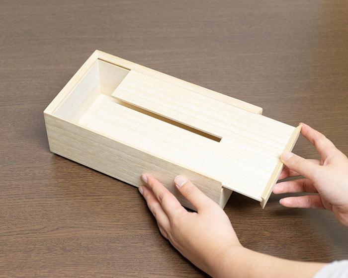 増田桐箱店のティッシュケースの蓋をスライドさせている