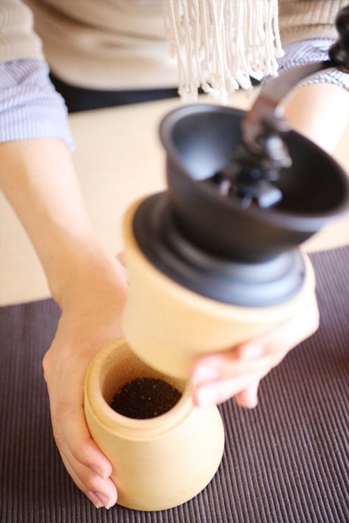 A woman twists the coffee grinder to remove coffee beans