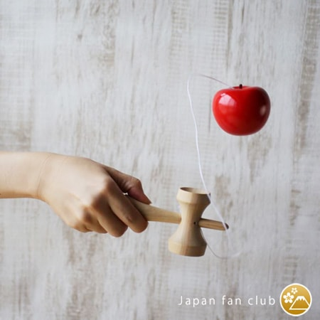 A woman is playing apple kendama