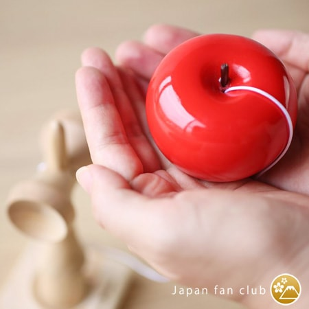 Apple ball of kendama on a woman's hand