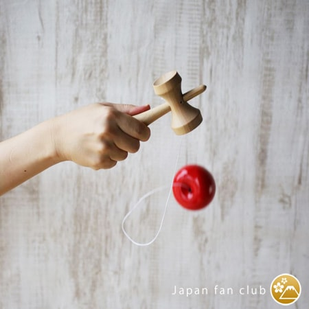 A woman is playing kendama