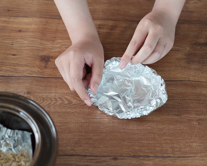A woman is making an aluminum foil plate