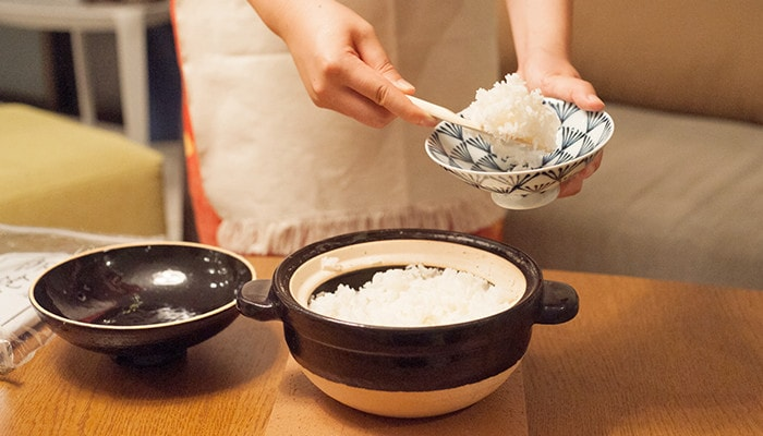 A woman is scooping rice from donabe rice cooker