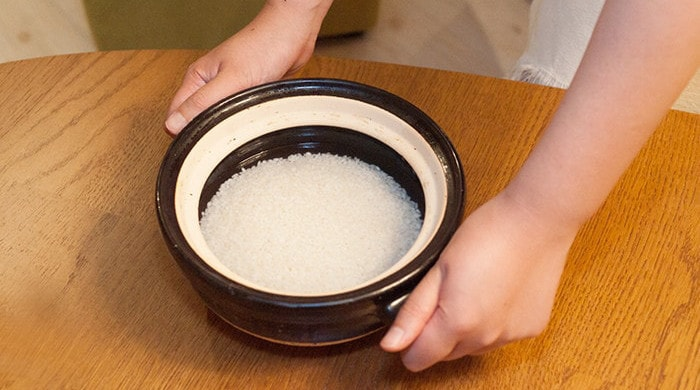A woman is having the handles of donabe rice cooker