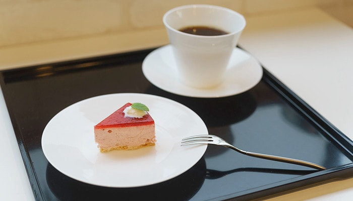 A piece of cake on the plate and coffee in the EXQUISITE cup