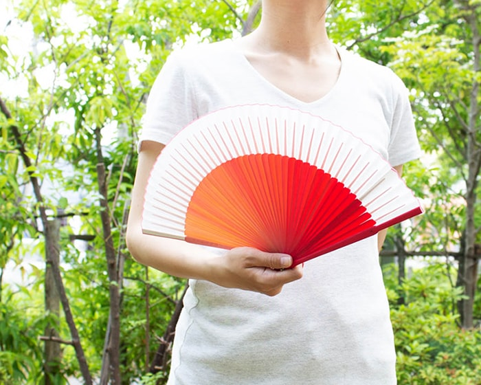 A woman is fanning pink gradation sensu fan