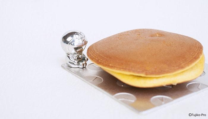 小皿の上に乗ったどら焼きをドラえもんが食べようとしているようなイメージ写真