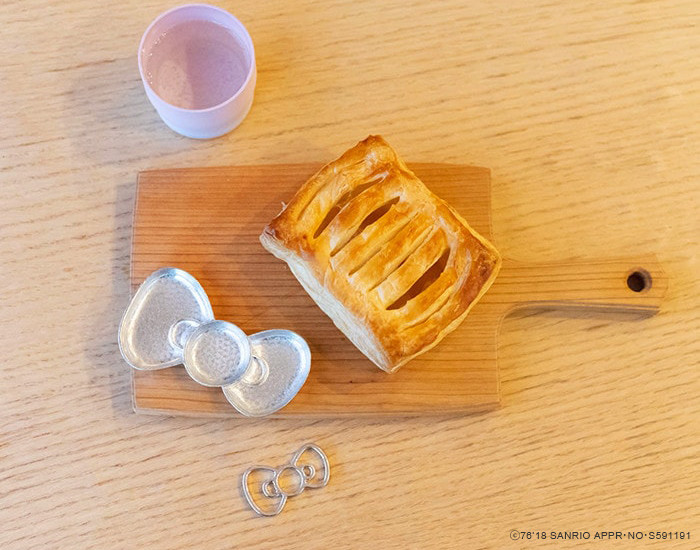 Apple pie and tin ribbon tray of Hello Kitty on a wooden cutting board