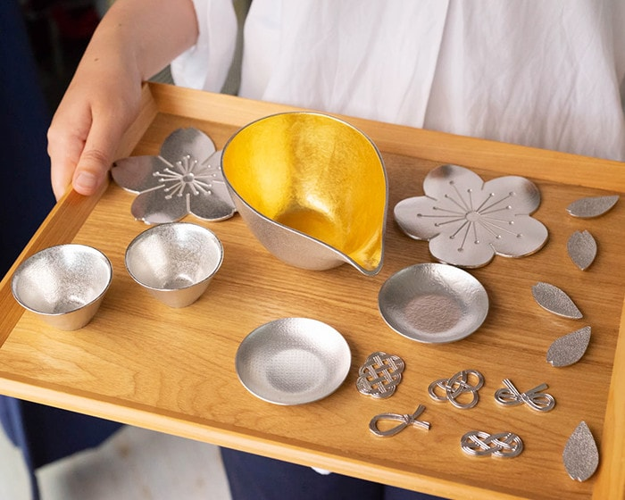 A woman brings various tin products of Nousaku with a wooden tray