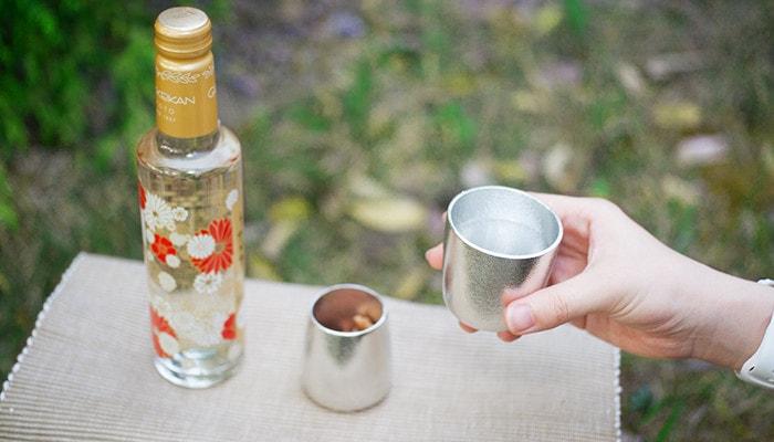 外でランチョンマットの上にお酒とナッツの入ったふたえ、そしてお酒の入った酒器をもっている様子