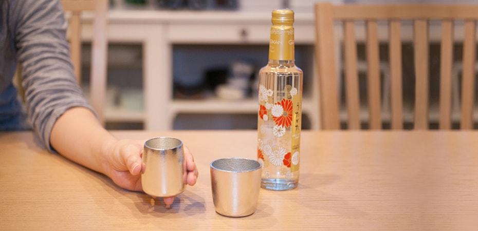 ダイニングテーブルに酒器とお酒が置いてあり、1つ酒器を片手に持っている様子