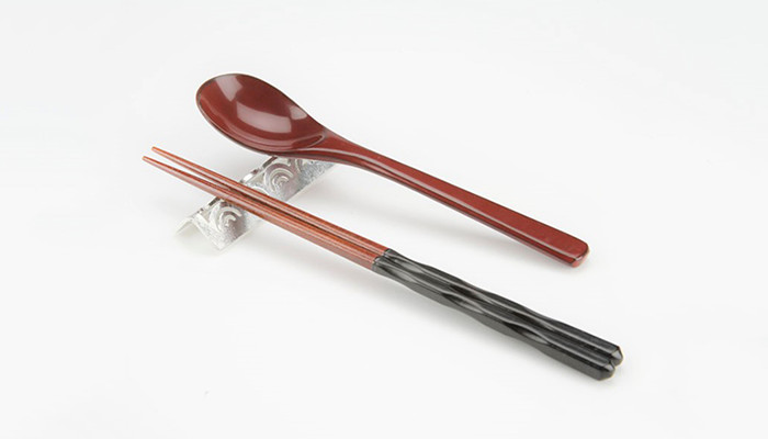 Red chopsticks and spoon on the cutlery rest Lucky motif