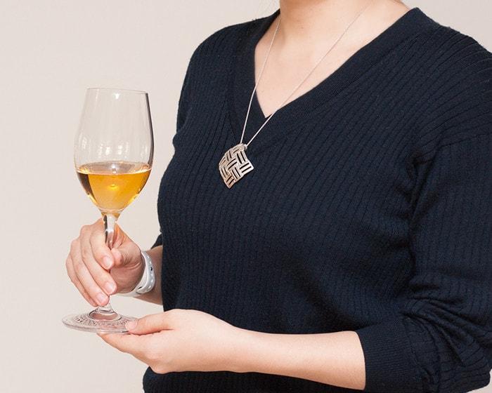 能作の錫アクセサリーを身に着けた女性がワイングラスを持っている