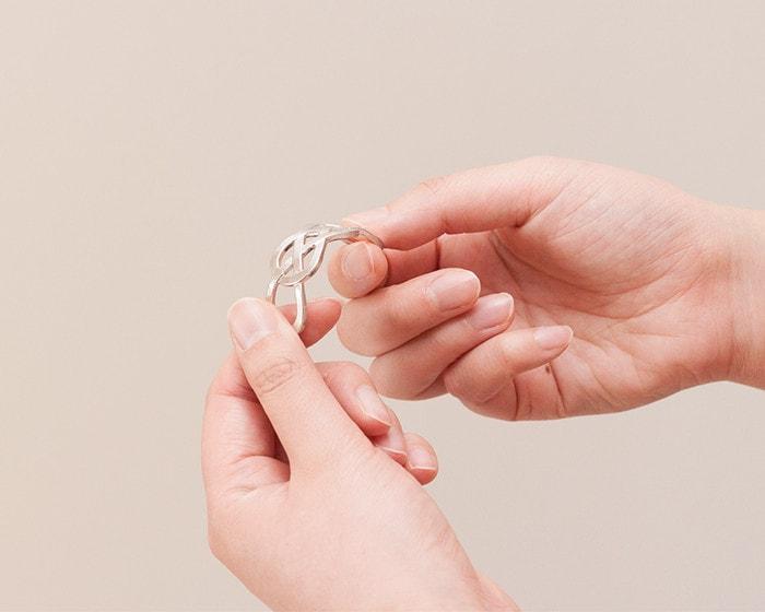 A woman bends tin jewelry of Nousaku