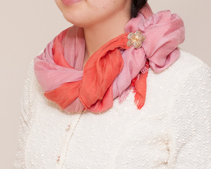 A woman wears red scarf and pin it with Japanese plum tin flower brooch