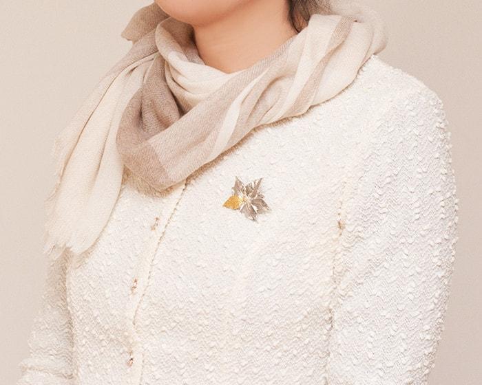 A woman wears Poinsettia tin flower brooch