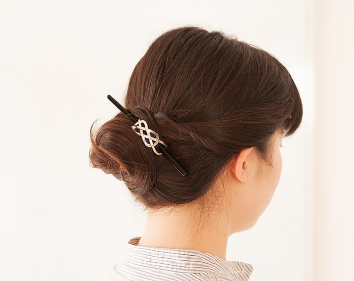 A woman wears hair barrette with stick Yui