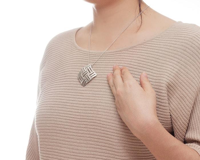 A woman wears tin pendant Aya