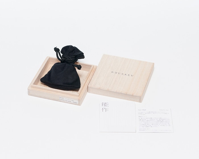 Tin pendant of Aya series within its exclusive drawstring pouch and paulownia box and its description paper