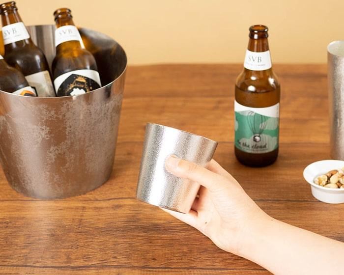 能作のNAJIMIタンブラーを手に持っていて奥にはクラフトビール