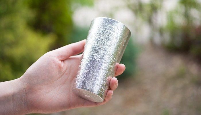 "A woman has tin coffee tumbler of ""Beer cup - white birch pattern"""