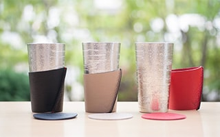 Tin coffee tumbler with leather coffee sleeve