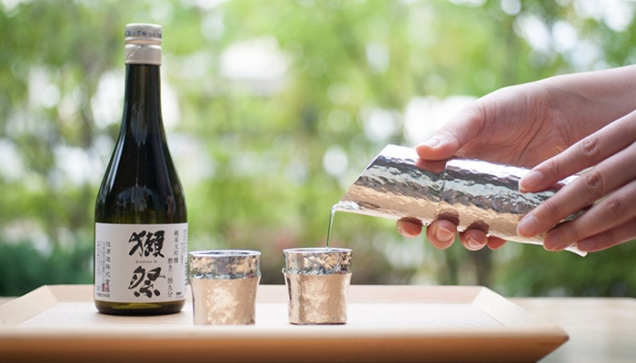 Pouring Japanese sake with bamboo katakuchi