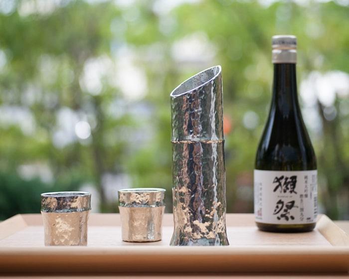能作の竹型高級酒器セットと、奥に獺祭
