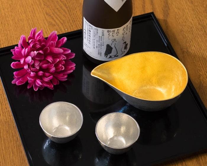 お盆に並んだ能作の酒器と日本酒の瓶を上から見た様子