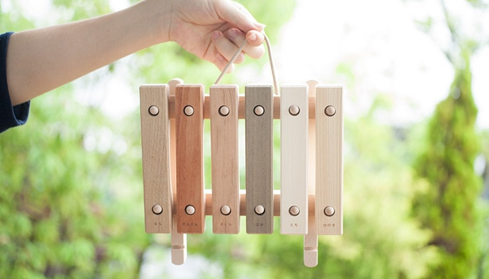 A woman is hanging the children's xylophone of Oak Village