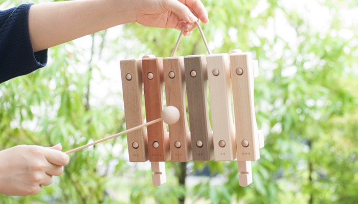 A woman is making sound with children's xylophone