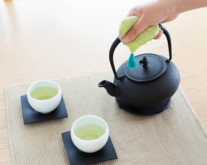 2客のお茶セットがテーブルに置かれており女性がRojiの南部鉄瓶を持っている