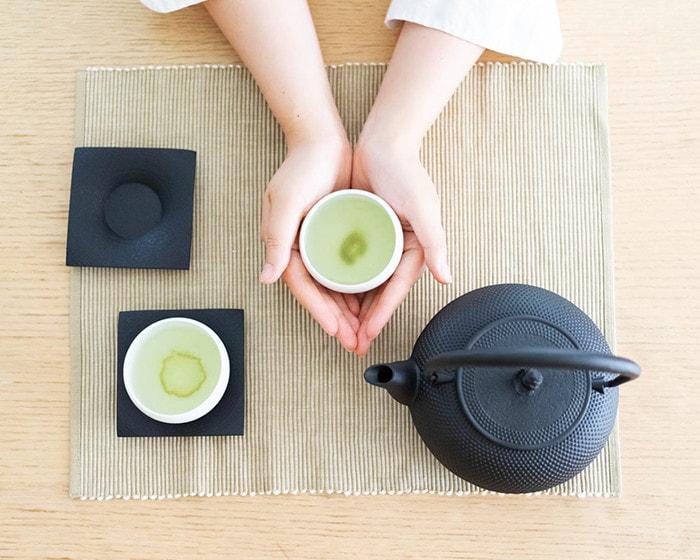 お茶の入った湯吞みを女性が両手で包むように持っている
