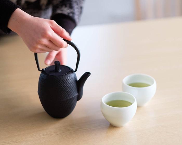 お茶の注がれた湯呑みが2つとカラーティーポット
