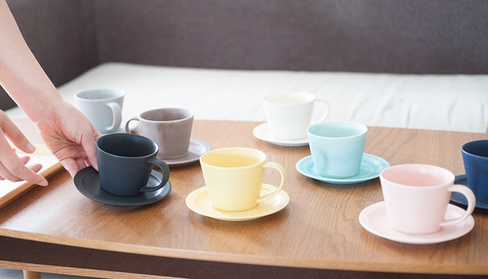 There are many pairs of cup & saucer on the table, and a woman has black one