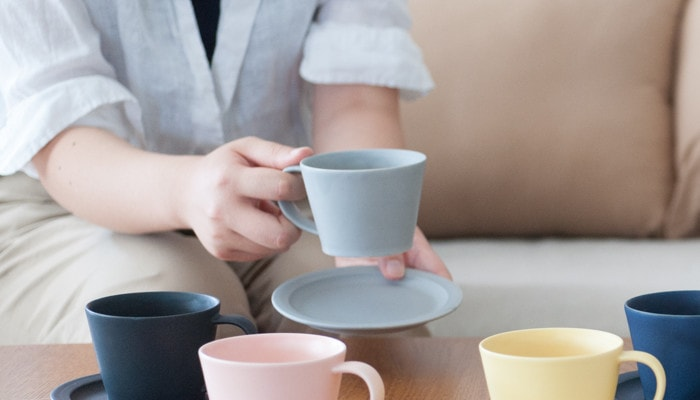 A woman has a cup with her right hand and a saucer with her left hand
