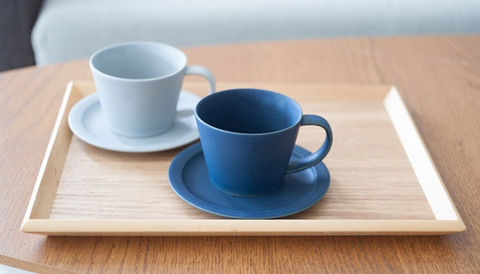 Gray and navy pairs of cup & saucer on the wooden tray