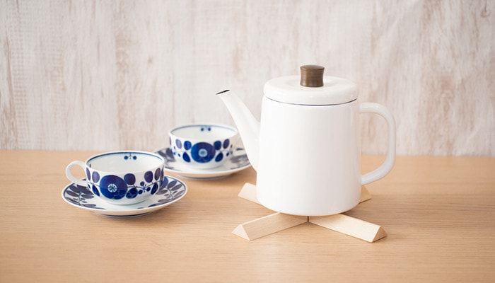 teapot with wooden kitchen hot pad
