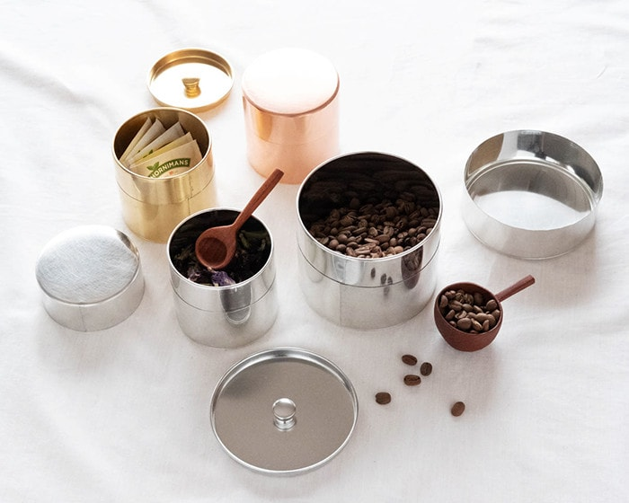 Coffee beans and tea bags in tin and brass tea caddies