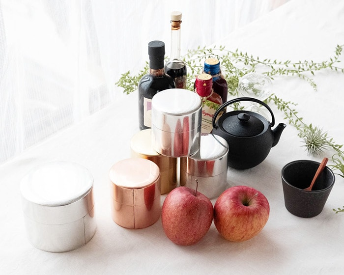 Tin tea caddies, apples, cup, and some other things make picture of still life