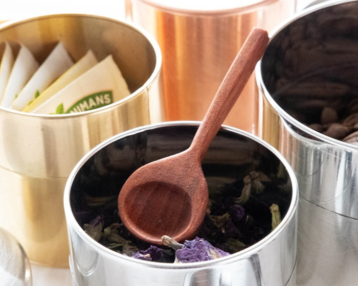 wooden teaspoon S and herb tea in tin tea caddy