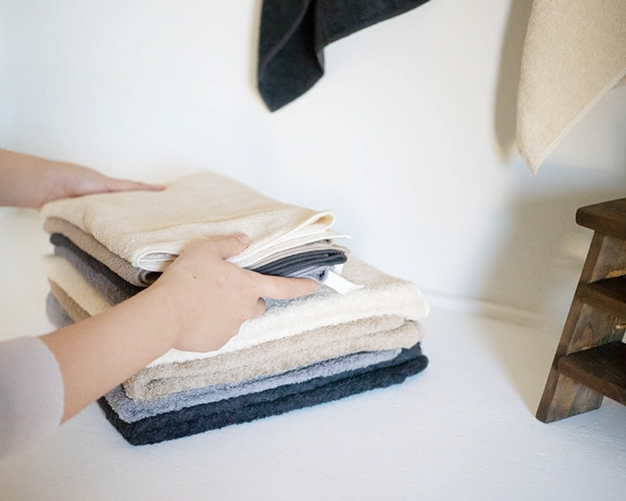 A woman piles up organic towels