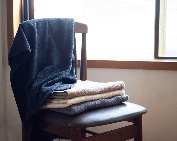 Piled up bath towels and a towel on backrest of a chair