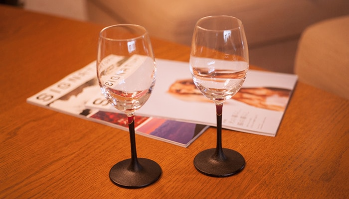 There are two lacquer colored wine glasses and magazines