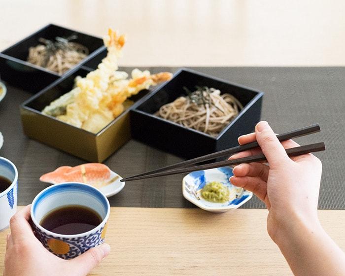 女性がそばを食べようと蕎麦ちょこと黒檀箸を持っている様子