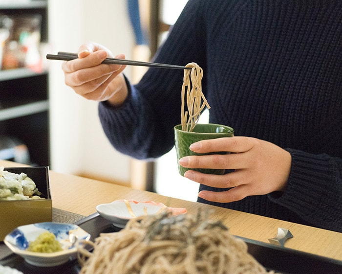女性が黒檀箸を使ってそばを食べている様子