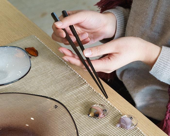 女性が両手で丁寧に六角黒檀箸を持っている