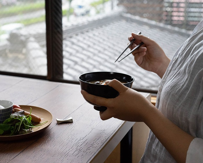 A woman is about to eat miso soup in the lacquer bowl