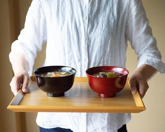 A woman serves miso soup in lacquer bowls with tray